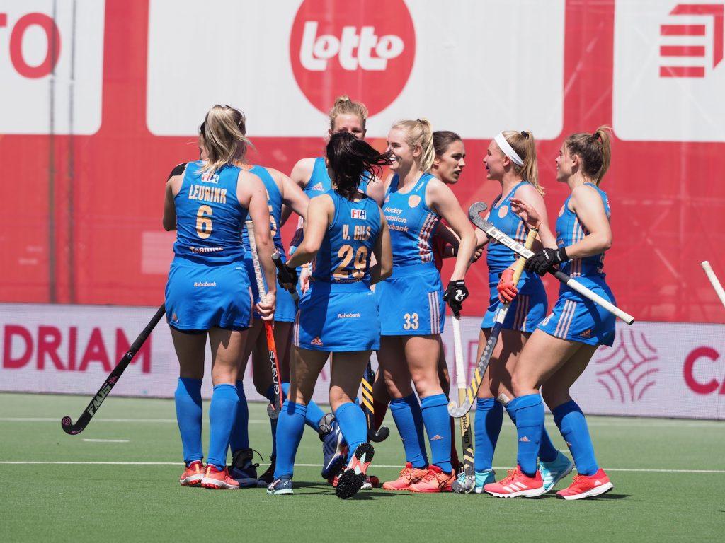 Stella van Gils viert met haar teamgenoten een doelpunt.
